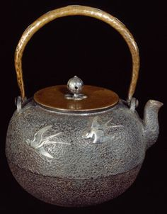 Tetsubin or tea pot of cast iron inlaid in silver with three flying swallows with gold eyes.