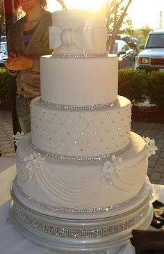 "My cake will look similar. Three tiers but the top and bottom tier will be all scroll work. (No ribbons or bow) There will be sapphire blue ribbon with rhinestones on each tier. The middle will be the same as the picture and the topper will be sapphire blue hydrangeas with our monogram ""C""! Perfect!"