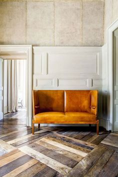 up-cycled wood floor yellow settee loveseat. off-center wood paneling on wall.  love all of it.