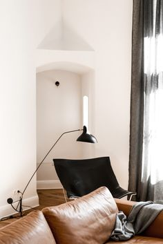 Squishy leather couch, wood floors, white walls and black details makes this modern living room just right.