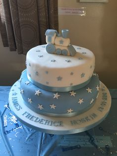 Boys Christening cake with stars and train cake topper. I made this cake for my Godson's Christening and used this link to help make the train cake topper; http://pin.it/fwhgbjO