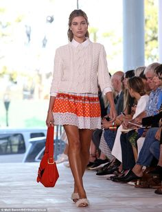 Spring chic: She wore a white knit sweater over a patterned orange and white…
