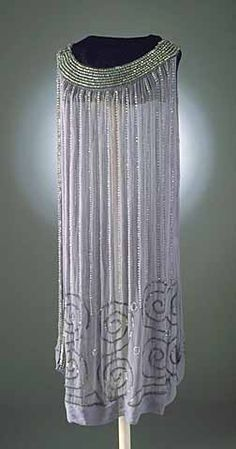 1920s dress of pale blue chiffon beaded with vertical rows of alternating transparent ball and cylinder beads ending in spiral designs at an uneven hem. The chemise dress hangs straight from the shoulders and is sleeveless with a scoop neckline. Front and back yoke are solidly beaded.
