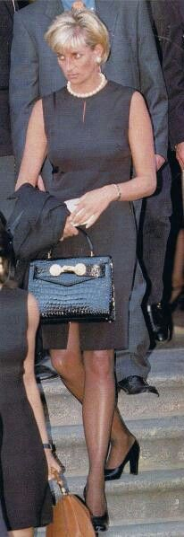 """22nd July 1997, Milan, Italy: """"The Princess of Wales was at Milan's gothic cathedralon 22 July 1997for the memorial service of her friend Gianni Versace, who once called her """"The Mother Teresa and Cindy Crawford of our time"""". She wears his black shift-dress and leather Kelly bag with Medusa heads, re-named """"the Diana bag"""". Diana comforted Elton John during the service. By a tragic twist of fate, he was to sing at her funeral service just a few weeks later."""" Comment: duchesseorange.."""