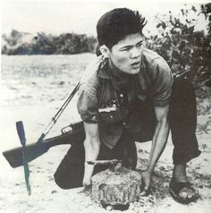 Vietcong planting IED. Difficult to fight a war when your enemy knows the landscape better than you.