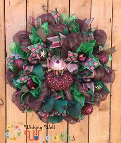 This Cute Christmas Elf Wreath is covered in beautiful maroon red and moss green deco mesh, on top of the mesh sits an adorable hand made Christmas elf doll this doll is covered in gorgeous fabrics of maroon christmas prints, and moss green stripes, the elf is adorned with golden tassels and moss green balls a cute hat rests on his darling faced head.