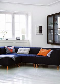a navy sofa seems like a neat idea in this copenhagen apartment..throw on some bright cushions too.