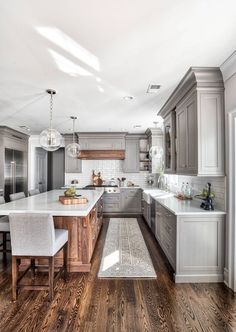 farmhouse kitchen. Grey cabinets, wood island and wood vent hood. Upper cabinets bottom trim flares so backsplash lines up perfect from counter to cabinets