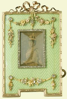 Fabergé rectangular strut frame of gold and pale green guilloché enamel with a notched base, the rose diamond bezel is inset with a photograph of Queen Alexandra in coronation robes. The border has a gold bead and reel edge mount, pierced ribbon crest and swags set with rose diamonds at top and base. Mark of Viktor Aarne, 1902. Given to Queen Mary when Princess of Wales by King George V when Prince of Wales, 1906.