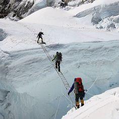 Climbers cross a treacherous crevasse in the Khumbu Icefall on Mt Everest.