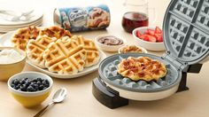 Waffle iron with waffles, waffles and toppings of sryup, strawberries, blueberries, peanut butter and butter