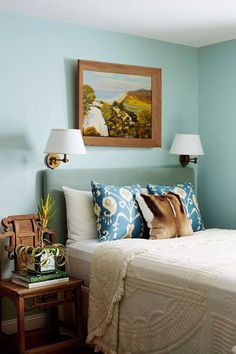 When space is limited and you don't want to shop for new, bulky furniture, use a chair as a side table and install wall sconces to save surface space. A cheerful color, like this pale turquoise hue, is also a good idea to set a happy mood.
