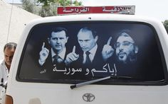 A poster showing Syrian President Bashar al-Assad, left, Russian President Vladimir Putin and Lebanese Hezbollah leader Sayyed Hassan Nasrallah, right, is seen on a micro bus in al-Qardahah town, near Latakia, as Syria is preparing to hold presidential elections.