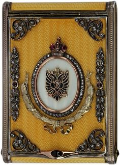 """A Fabergé silver, gold, and gem-set Imperial presentation cigarette case. Late nineteenth-century. Of rectangular form with rounded corners, the surface of the case cast and enameled. The lid embellished with a gold and diamond Imperial eagle surrounded by a series of faceted colored gem-stones, applied cast silver and gold wreath and laurels, Ruby thumb push closure. Total of 106 diamonds, five ruby's and two sapphires. Faberge hallmarks to body and lid including """"FABERGE"""" in Russian, ..."""