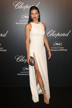 The Brazilian supermodel posed for photos at a party hosted by Chopard in a white gown with a high slit on one side and a cutout on the other one.