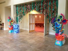"""Entrance to the Sanctuary --- Paper flowers, on pool noodles  & paper vines curtain. The vines were cut long strips, then we cut diagonals down the strip to look like """"leaves"""". Then just scrunched the paper."""