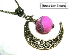 """This necklace was handcrafted by me. I used a bronze filigree crescent moon charm and added a bronze spacer bead and a beautiful bright pink druzy agate bead. The pendant hangs almost 2.5"""" and comes on your size of bronze link chain."""