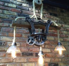 In a tribute to the farming tools of days ago, here is a hanging light fixture has been custom built around an antique cast iron Olson hay trolley and pulley. This is not a reproduction, but genuine farm fresh items that have been cleaned and refinished. The modern electrical wiring has been cleverly wrapped, hidden, or embedded into the fixture. The trolley is mounted to a reclaimed wood beam, just as it would have been in a barn when it was a working trolley.    The lamp is shown with two…