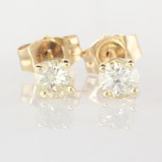 Beautiful diamond stud earrings set in 14k yellow gold. The stones measure 3.38mm diameter or approximately 0.30 carat total. These diamonds offer a lovely sparkle in a modest size. The diamonds appear bright, clear and eye clean. Under 10x magnification there are no dark black inclusions but there are light to yellow colored feathers visible. Please zoom in on the images for gem clarity. Diamond color will vary slightly with the lighting and background. The earring stems are stamped 14K and…