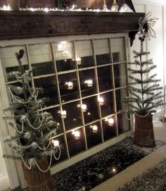Down to Earth Style - old window as fireplace cover with candles - via Remodelaholic