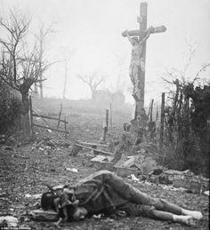 """Carnage: En medio de la devastación y los cuerpos de los soldados muertos atrozmente, un crucifijo se yergue. Milagrosamente preservada del fuego de artillería. La poderosa imagen fue capturada después de una escaramuza sangrienta en 1917 por el foftógrafo de 17 años, Walter Kleinfeldt, su hijo ha dicho respecto a esta imagen """"Esta fotografía es como una acusación, una acusación contra la guerra""""."""