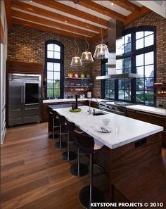 love the wood floors, the brick, and the tall windows. don't mind that nice fridge, the awesome range, or the huge island either.