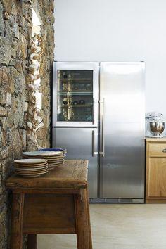 Frigorífico en metal que se encuentra en la cocina. Está detrás de esta pequeña mesa donde hay algunos platos. El frigorífico es muy grande y tiene también el congelador y un espacio para los dulces.