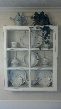 I used an old window and cedar fence boards to make this China cabinet. Put grooves in the shelves for holding dishes, painted and antiqued it :)