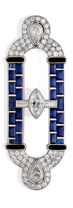 An Art Deco sapphire, diamond, black onyx and platinum brooch. Dimensions: 2 1/4 x 5/8in.