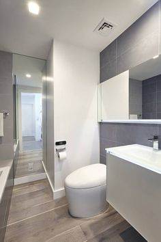 Minimalistic bathroom in grey & white with wooden floor boards by Andrew Mikhael Architect.
