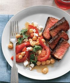 Steak With Chickpeas, Tomatoes, and Feta|A refreshing salad of crispy chickpeas, Feta, tomatoes, and cilantro lightly dressed with lemon juice makes a tangy counterpoint for seared strip steak. Look for beef that has plenty of marbling (streaks of fat)—the meat will be more flavorful.
