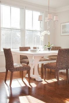 Beautiful cottage dining room features a Vendome Small Chandelier illuminating a white trestle dining table lined with wicker dining chairs. Circa Lighting dining room