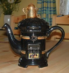 French Stove teapot, in shape of black woodburning stove or woodstove, with gold kettle as knob, ceramic