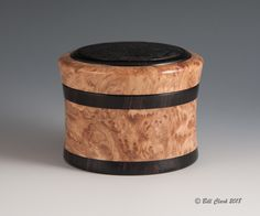"""Bill Clark - This threaded lid box entitled """"Dragonflies and Cattails"""" has slightly concave walls that grow with an increasing diameter to the lid which is larger than the base. This form style breaks from the traditional straight walled boxes and gives the box more visual appeal. The woods are Tasmanian Rose Burl and African Blackwood. The etched image on the top is a variation of my familiar cattail design. The box is 2 1/2"""" tall."""