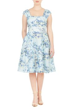 Floral print patterns our feminine A-line organza dress styled with solid banded stripes at the waist to cinch in the look.