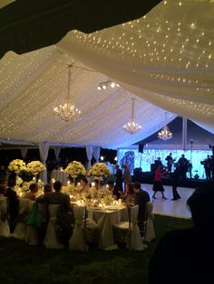 Get Lit twinkle lights in a sheer fabric lined tent.  Crystal chandeliers and highlighted head table flower arrangements complete the lighting design.