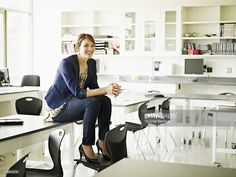 Stock Photo : Smiling teacher sitting on desk in classroom