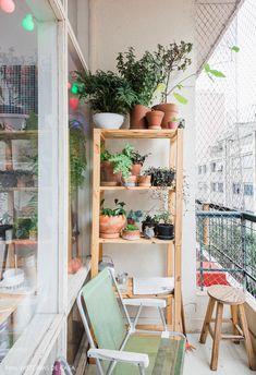 Varanda pequena com estante de madeira com plantas, cadeira de praia e luzinhas coloridas.