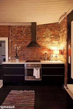 Unelmien hirsitalo | Uusi keittiö sijoitettiin yhteen asuinhuoneista, aivan vanhan keittiön viereen. Leivinuunin taakse kätkeytynyt tiiliseinä kaivettiin esiin, ja siitä tuli uuden keittiön keskipiste. Tiiliseinän vastapainoksi valittiin musta moderni keittiö.