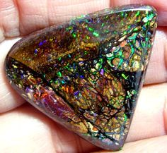 "Boulder opal. Similar to black opal except that the foreground colour is very thin and sits on a brown ironstone base. These stones at times can come with interesting ""hills"" and ""valleys"" on the surface."