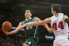 Travis Trice goes up for a shot around Wisconsin forward Frank Kaminsky on Feb. 9, 2014, at Kohl Center in Madison, Wisc. The Spartans lost to the Badgers, 60-58. Danyelle Morrow/The State News