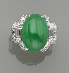 A jadeite jade and diamond ring  centering an oval-shaped jadeite jade cabochon, measuring approximately 17.40 x 12.30 x 7.95mm., flanked by baguette, round brilliant, and single-cut diamonds; mounted in platinum.