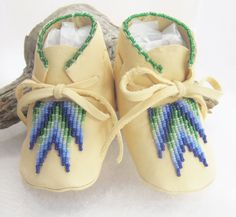 Authentic Native American made baby moccasins of soft deer hide in a southwest bead work design.