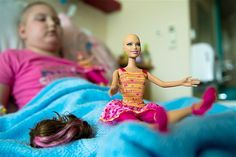 July 22, 2013: Nikola Cichowczyk, 8, plays with one of 12 bald Barbie dolls at Jurasz University Hospital in Bydgoszcz, Poland, on July 19. The Jurasz Hospital is the only one in Poland where children recovering from chemotherapy can play with specially designed Barbie dolls. The Mattel Company created the bald dolls for young patients who have lost their hair due to cancer treatments or other medical reasons. The dolls are not for sale at retail stores