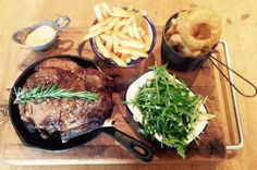 Sunday roast cote de boeuf. Rib of beef roasted in skillet, served with rocket salad, beer battered onion rings, fries & béarnaise sauce.