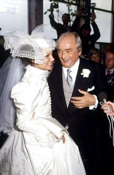 SIMON SPIES & JANNI: Holmens Kirke, København, 11. maj 1983.Kjolen i silke, tyl, kniplinger og blonder kostede 175.000 DKK, vejede 25 kilo og var meget opsigtsvækkende og typisk for 80'erne - netop som prinsesse Dianas. Og akkurat som prinsesse Diana druknede Janni lidt i den store kjole med de mange detaljer og knapper. Jannis brudekjole er for øjeblikket udstillet på Sophienholm sammen med en række af Jean Voigts andre couturekjoler. Simon Spies døde året efter.