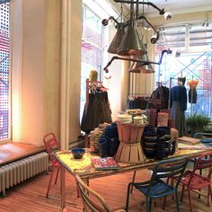 Merchandising; love the baskets and the industrial light fixtures, with the chairs too, yesss