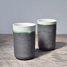 Zwei handgefertigte schlanke Becher aus dunklem Steinzeugton. Die Aussenseite ist matt anthrazit glasiert, die Innenseite weiß glänzend. Wo sich beide beiden Glasuren treffen entsteht ein sehr schöner grünlicher Streifen.Jeder Becher ist ein UnikatHandgemacht in einer kleinen Keramik-Werkstatt in Niedersachsen. Sie wurden an der Drehscheibe gefertigt. Du kannst beide Becher in die Spülmaschine stellen und Dein Leben genießen.Höhe: 11 cmBreite: 7,5 cmVolumen: 230 ml