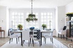 In the dining room, an iron chandelier designed by Kristina Lindhe is filled with an arrangement of ivy pots and candles; Artwood chairs surround the antique table. The hutch is a family heirloom. #NYC&G