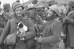 George Orwell holds a puppy during the Spanish Civil War in 1937. Ernest Hemmingway can be seen in the background.